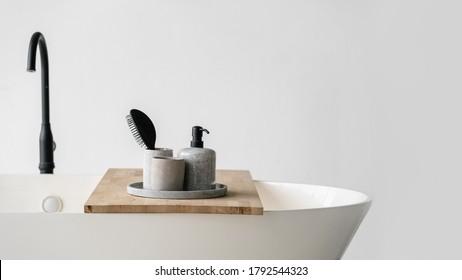 Modernes Badezimmer mit Badewanne und Wasserhahn. Panoramasicht auf die Fächer mit Haarbürste, Seife in Flaschenspender und saubere Handtücher in der Holzablage auf weißem, zeitgenössischem Bad bei schwarzem Wasserhahn
