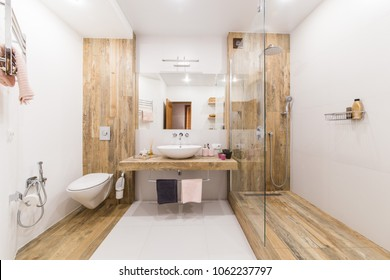Modern bathroom interior combined with toilet. Shower room and toilet are covered with tiles in the color of wood, white walls and a white floor and a washbasin with a large mirror in the center