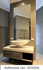 Modern bathroom interior design. Beautiful mirror, basin, faucet etc.