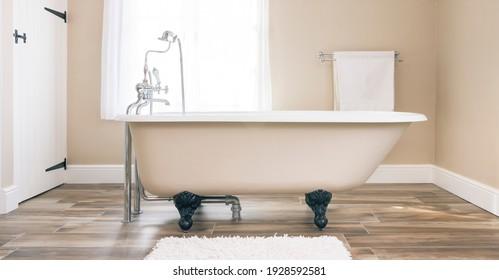 El moderno diseño interior del cuarto de baño incluye una bañera de pies a las nubes y suelos de baldosas. Lujo, baños contemporáneos, Reino Unido.
