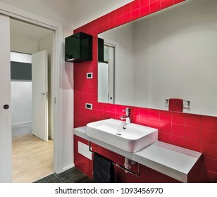 modern bathroom interior in the foreground  the big mirror and the counter top washbasin, the wall are coating of red tiles