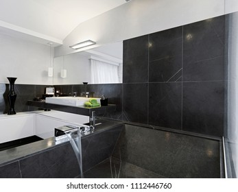 modern bathroom interior in the foreground the masonry bathtub coated of black marble as well as the walls  in the background the countertop washbasin on a plane always of black marble