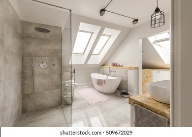 Modern bathroom interior with minimalistic shower and lighting, white toilet, sink, bathtub and roofwindows