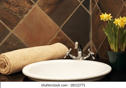 Modern bathroom interior with rolled up towel on the counter and daffodils in the background