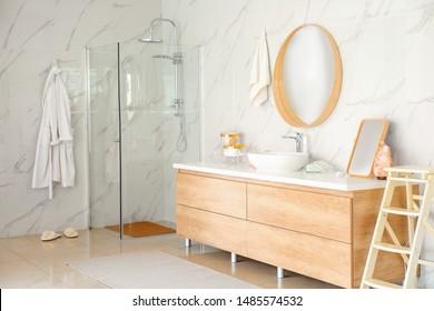 Modern bathroom interior with shower stall, vessel sink and round mirror