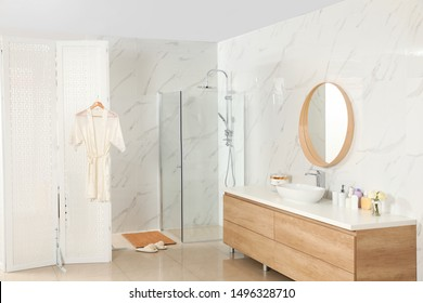 Modern bathroom interior with shower stall and folding screen