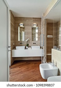 modern bathroom interior with wooden floor in the foreground the bidet in background the sink cabinet with two counter top washbasins on the right the masonry shower cabin with galss door