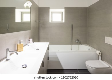 Modern bathroom with large brown tiles and large mirror. Nobody inside