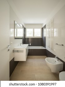 Modern bathroom with large dark tiles. Nobody inside