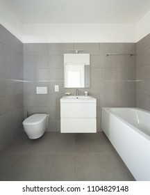 Modern bathroom with large tiles in newly built apartment. Nobody inside
