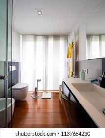 Modern bathroom with light and dark tiles. Nobody inside