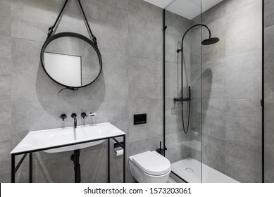 modern bathroom in neutral colours with black fixtures, round mirror and minimalist shower