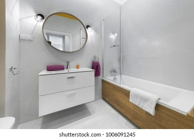 Modern bathroom with oval mirror in stylish apartment