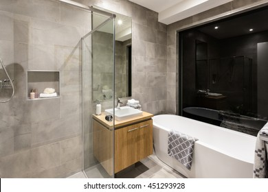 Modern bathroom with a shower and bathtub next to a mirror and tap with washstand illuminated at night