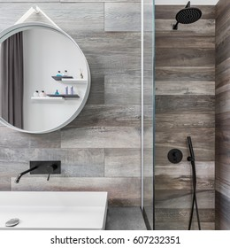 Modern bathroom with shower, round mirror and wood effect tiling