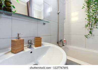Modern bathroom sink basin faucet paired with wooden soap containers.  Concept of cleaning the bathroom and freshness. Green herbs and flowers next to bath