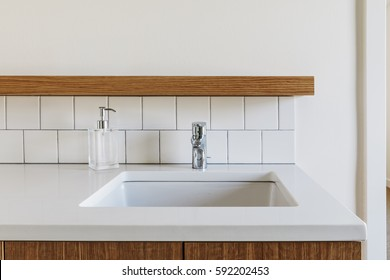 Modern bathroom sink with subway tile backsplash with wood details.