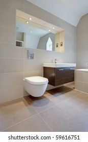 modern bathroom suite with wall mounted wc and sink unit and large mirror