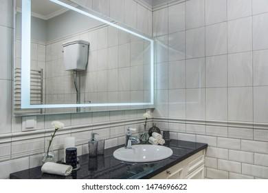 Modern bathroom with bathroom vanity, sink and large backlit illuminated mirror
