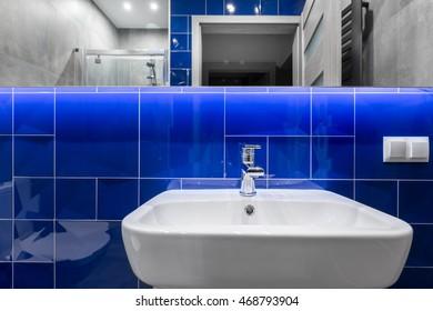 Modern bathroom with washbasin, mirror and shiny blue tiling