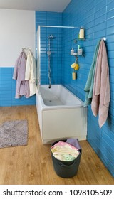 modern bathroom with white bath, shower, laundry basket and blue tile