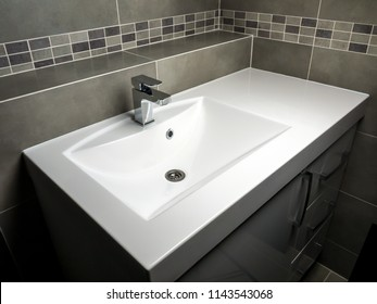 Modern bathroom with white washbasin with chrome faucet and gray tiling