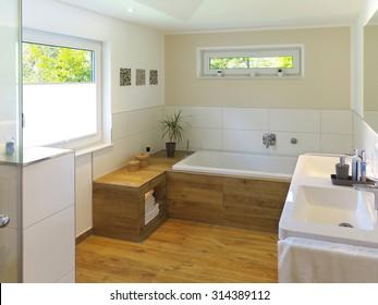 modern bathroom with wooden floor, bathtub, sink and windows