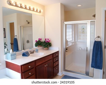 Modern Bathroom with a wooden vanity, glass door on the shower, and a large mirror with lights above.