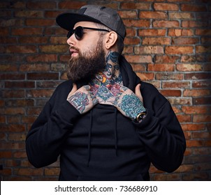 Modern bearded hipster male with tattoos on his arms, dressed in a military jacket posing over vintage wall from a red brick.