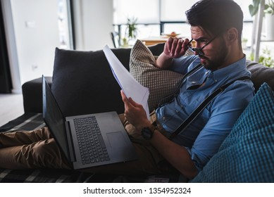 Modern bearded young businessman working on laptop computer while sitting on sofa at home, looking at some documents