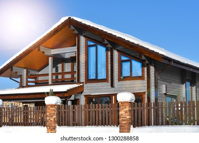 Modern beautiful grey wooden house and blue sky. Winter natural photo.