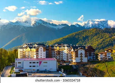 Modern beautiful houses on the background of large snow-capped mountains and a green spring sunny forest. Mountain Olympic Village, Rosa Peak Ski Resort, Sochi, Russia.
