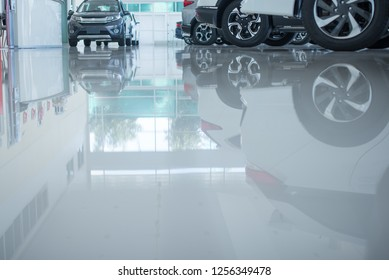 Modern beautiful showroom with cars being sold.  The underside of a car is reflected by the smooth