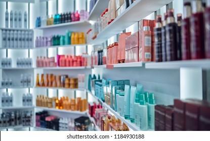 Modern beauty salon interior. Different cosmetics on shelves.