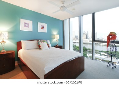 Modern bed room and lamps, comfortable area with designs, walls are white color, pillows are beautiful, inside rooms of a apartment,  city view close to river.