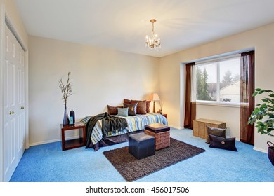 Modern bedroom with blue carpet floor and dark brown curtains