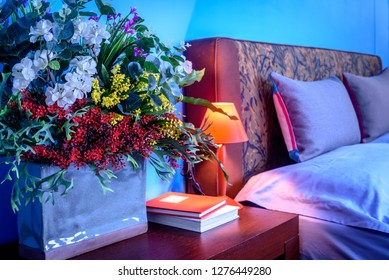 Modern Bedroom decoration with headboard, wooden table & colorful artificial flower vase / Home improvement design concept