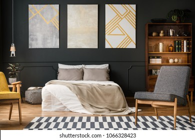 Modern bedroom interior with big bed, grey and white carpet, chairs, paintings, lamp and bookcase with books and decorations