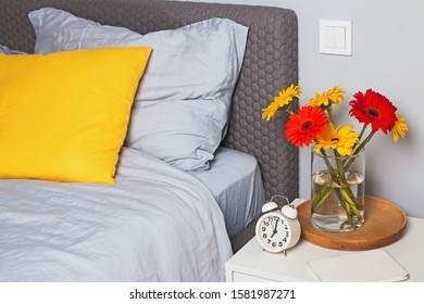 Modern bedroom interior with bright decorative pillow on the bed and brigh flowers on the nightstand.