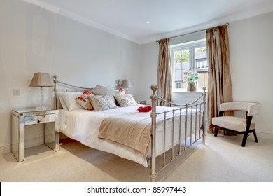 Modern bedroom interior with fashionable fabrics and furniture including traditional bedstead