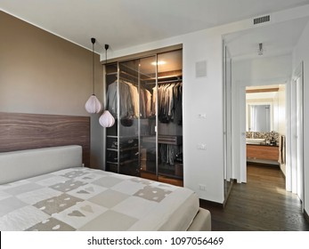 modern bedroom interiors with wardrobe overlooking on the bathroom in the foreground the bed