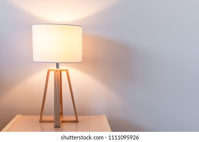 Modern bedroom lamp lit against white wall with copy space