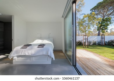 Modern bedroom with large window to garden