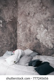 modern bedroom in loft style in white and gray colours. white bedding. textured gray wall. many pillows white, grey, black.