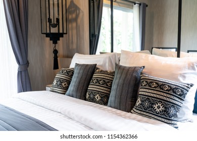 modern bedroom with many pillows on bed