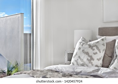 Modern bedroom pillows with a blanket and a glass window that viewing outside