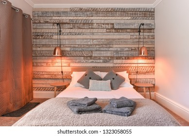 Modern Bedroom with rustic wooden headboard and white linen and pillows, copper lamp shade - Airbnb accommodation