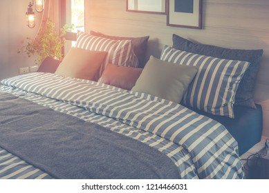 modern bedroom with set of pillows and stripe pattern blanket on bed, interior design decoration concept