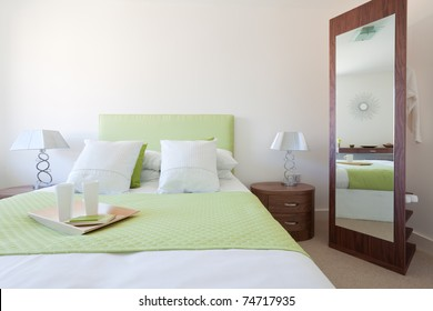 Modern bedroom suite with lime green quilt and headboard, white duvet and pillows, side table with lamps and mirror