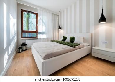 Modern bedroom in white finishing and wooden floor